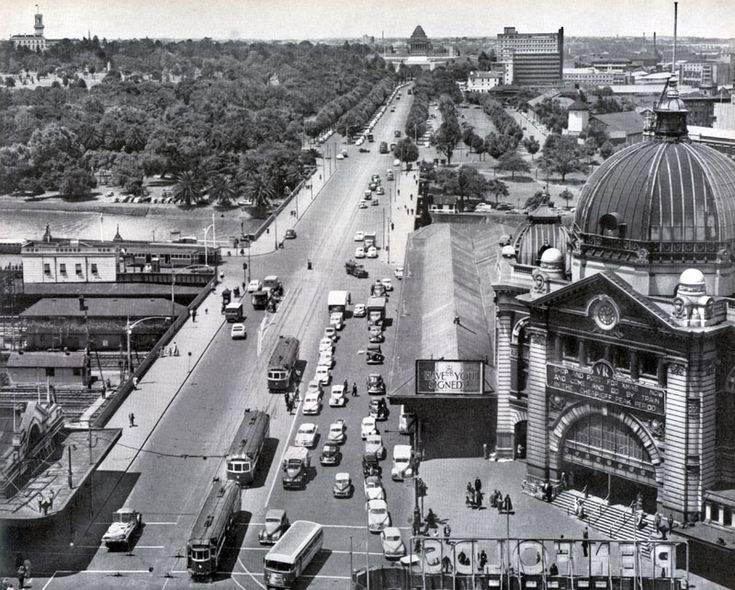 Vintage Melbourne, Australia. Swanston Street, looking down St. Kilda Rd, Probably mid-20th century. Flinders St. Railway station on right with Princes Bridge Railway station on the left. (now site of Federation Square). And no Art Centre. Shrine of Remembrance centre background.