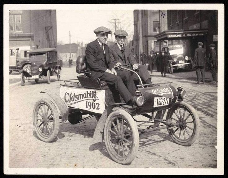 """Photographed on George Street in Stratford Ontario Canada in 1925. This 1902 Oldsmobile was a part of an organized new car showing for a local car dealer """"Roy Brothers Garage"""" at 108 Downie Street. Seated in the Oldsmobile on our left is the 1st NHL Hockey Superstar Howard """"Howie"""" Morenz who played for the Montreal Canadiens from 1924 till 1937. Morenz 1902-1937 started his hockey career in Stratford before joining the Montreal NHL team. Seated with Howie is life time friend Walter """"Butch""""…"""