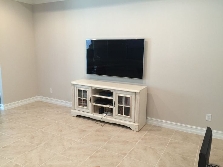 A TV mounting we performed overtop a white entertainment cabinet!