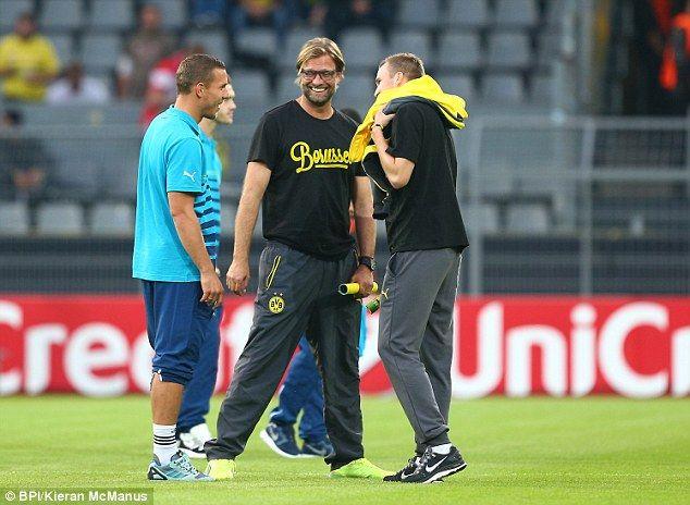 Lukas Podolski (left) chats with Jurgen Klopp (centre) and Kevin Grosskreutz (right) prior...
