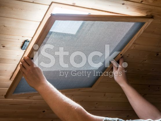 Installing homemade mosquito net on velux window on ceiling royalty-free stock photo
