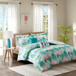 featuring a refreshing color palette of blue green and coral the comforter showcases oversized tropical plants that mimic the appearance of a lush