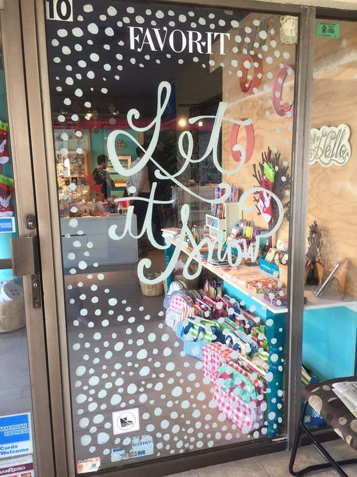 Boutiquizing Inspo: If this door could talk it would probably yell: 'Welcome to Christmas!' Or, in a more accurate way, it would say: 'Let it Snow'. Either way, this piece successfully mixes loopy calligraphy and swirling snow to create a winter wonderland effect. Trendwatch: Liquid chalk markers \ Single colour \ White \ Calligraphy \ Window art \ Christmas & Winter. Artwork by Mónica Ríos @mokeumi