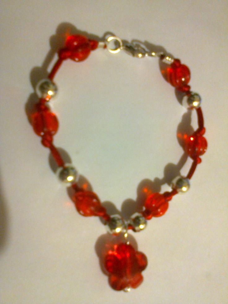 KA_P005 - Pulsera en color rojo, plata y colguije en forma de flor, con broche metálico.