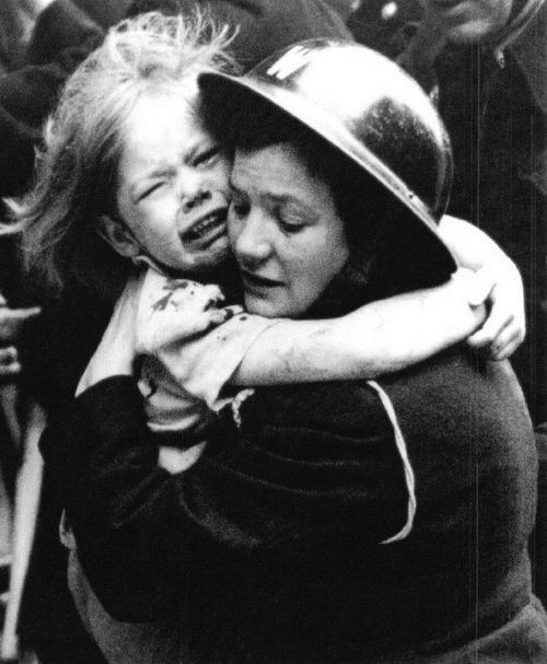 A female air-warden carries a little girl after she had been rescued from her bombed home. England, The Second World War.