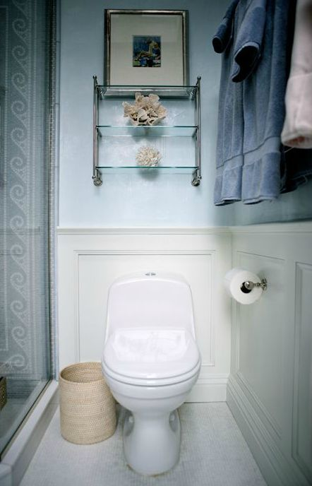 Ivory and blue bathroom features above the toilet glass shelves on blue walls paired with ivory wainscoting over white mosaic tiled floor next to corner shower with white and blue mosaic tile shower surround.