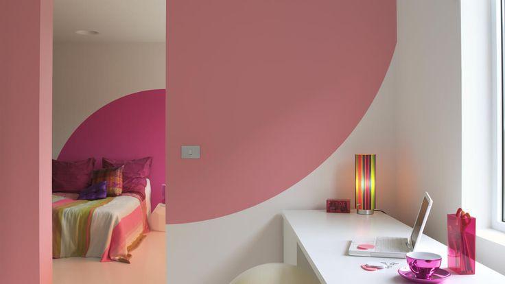 Uitbundige roze accenten brengen deze overwegend witte slaapkamer tot leven.