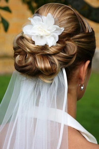 Braut unter dem Schleier mit locker geschlungenem Chignon-Brötchen und Blumen-Brauthaar