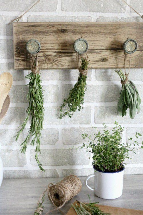 Here's what you'll need: – An old wooden plank – Three (or more) drawer knobs – Drill – Jute twine – Two eye hooks – Fresh herbs