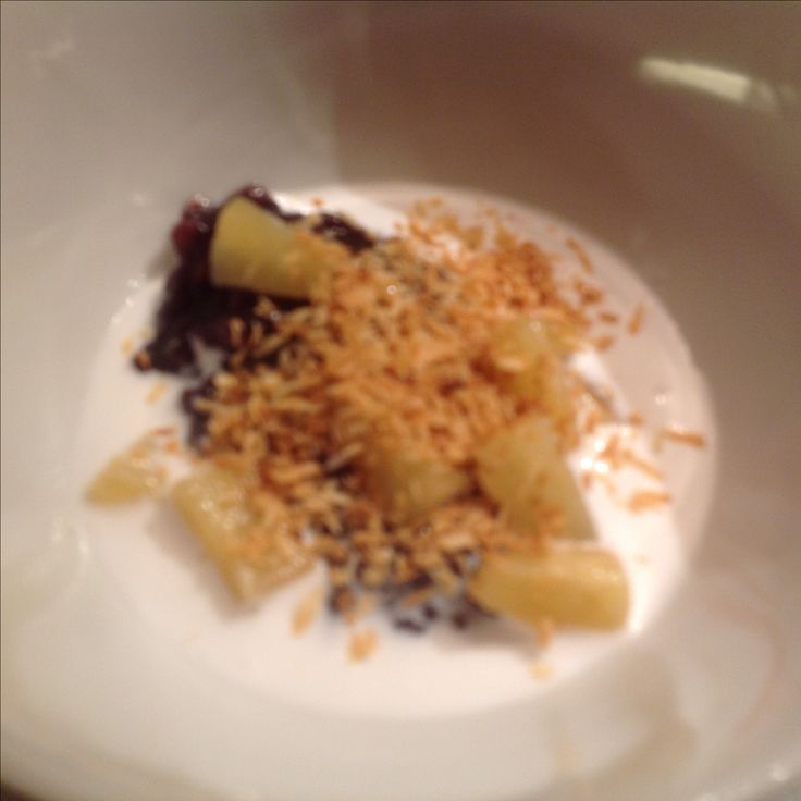 Black rice pudding with roasted coconut and pineapple and a coconutcream