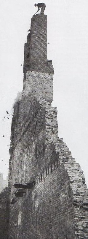 A workman perched atop this shaky chimney, all that is left of the building, is chipping away with a hammer. London during the Blitz, 1940.
