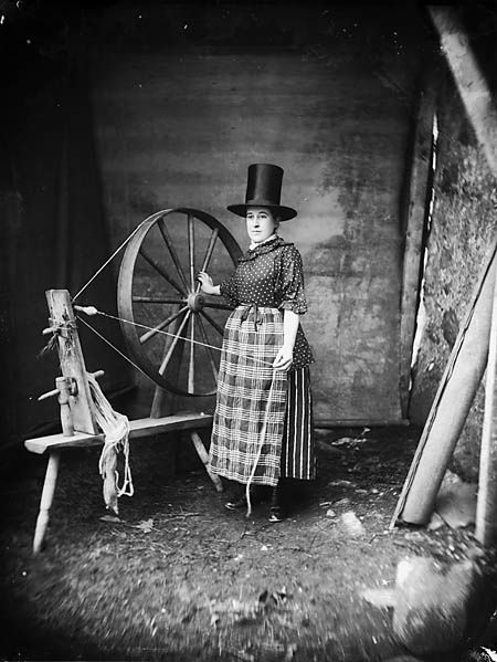 """A woman in """"Welsh national"""" dress with a spinning wheel - like the old wheel at Destrehan."""