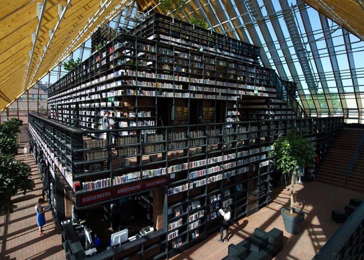 """""""Architecture firm MVRDV designed this magnificent library called Book Mountain, literally a mountain of books covered by a glass shell. The public library, located in Spijkenisse near Rotterdam, sits in the market square and serves as an invitation for visitors to come in and take a gander at the giant selection of interesting books shelved within the five-story structure."""""""