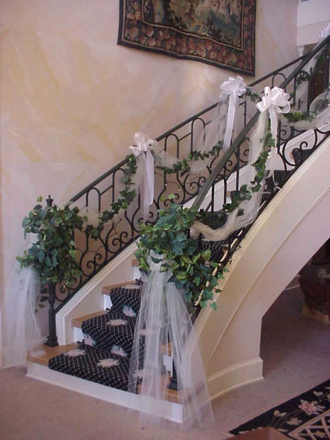 ceremony or reception staircase with tulle, flowers, and bows