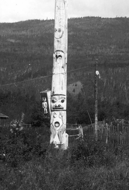 This is a detail of the lower section of the pole, showing an engraved Halibut that is followed by a Split-Eagle. At the base of the pole is a Bear's-Den-Person, a human figure with a hole in the centre of the body to represent the opening to the bear's den, and then a Drum or Drum-Person that is attached to the right side of the pole.