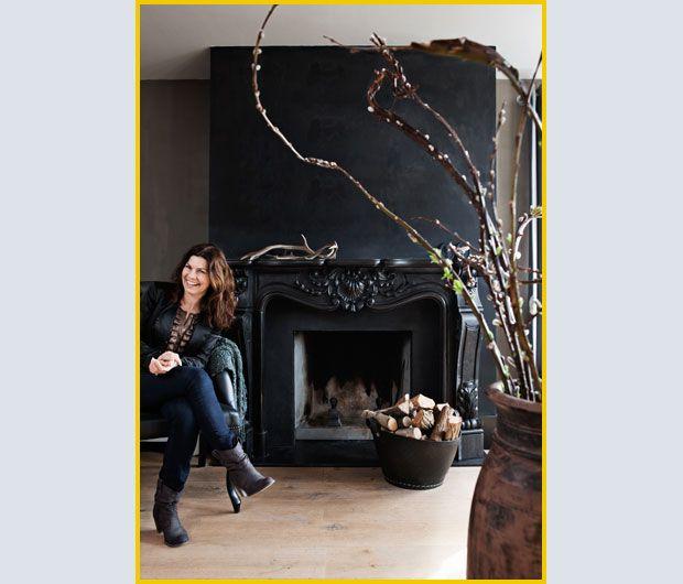 La decoratrice d'interni e padrona di casa Ineke van den Berg è ritratta accanto al camino, rinnovato con la vernice nera opaca Graphit (dell'azienda Carte Colori).