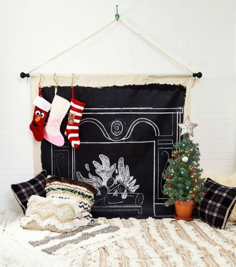 If your home doesn't come with a cozy fireplace make your own by coating a canvas in chalkboard paint, then adding decor details with a stick of the white stuff. The best part: Your mantle can be as traditional or modern as you like!