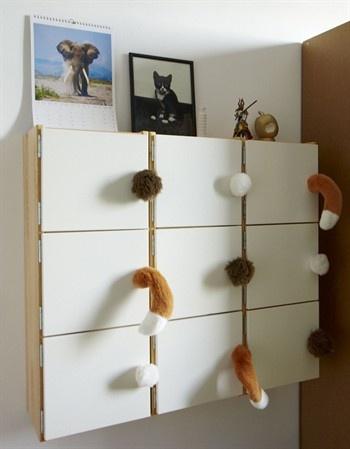 Des queues de peluches sont utilisées comme poignées sur un meuble de rangement dans une chambre d'enfant