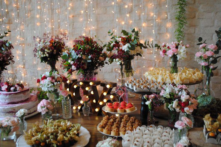Destalhe da mesa de doces com decoração nas cores Marsala e rosa em casamento romântico e rústico com fio de lâmpadas no fundo, parede de tijolos e letreiro cobre com lâmpadas vintage