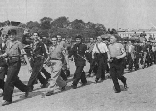 French Resistance fighters march alongside tanks of General Leclerc's 2nd (French) Armoured Division following the liberation of Paris, August 1944. Note that the Resistance file includes two Paris Agents de Police in uniform.
