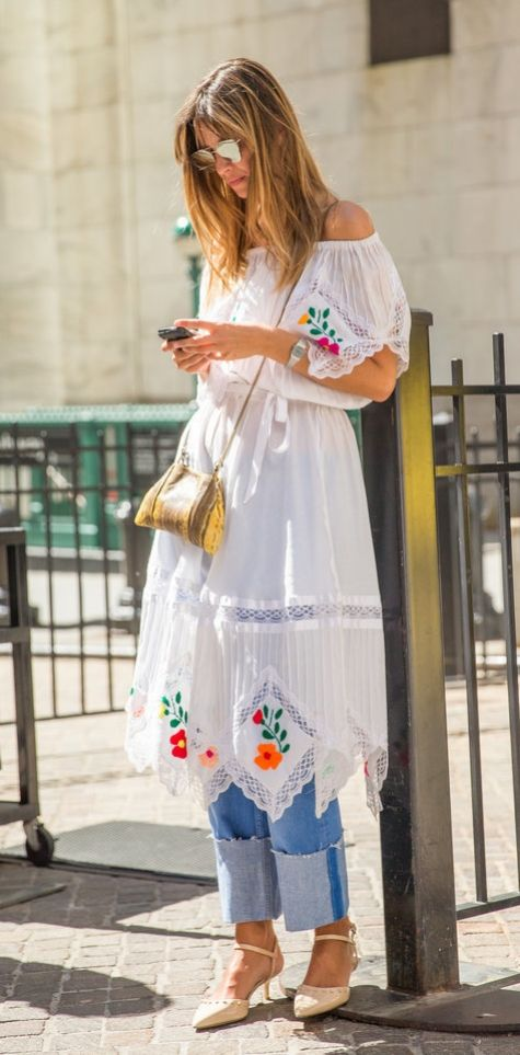 An embroidered lace dress over jeans