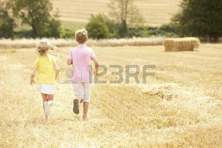 Kinder Running Through Sommer geerntet Feld Lizenzfreie Bilder
