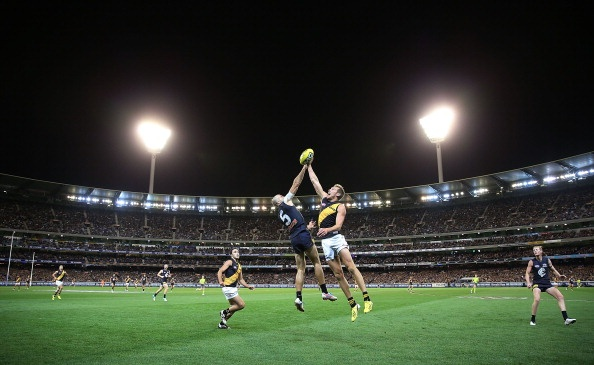 MELBOURNE, AUSTRALIA - MARCH 28: A Chris Judd (L) of the Blues contests for the ball against Luke McGuane of the Tigers during the round one AFL match between the Carlton Blues and the Richmond Tigers at Melbourne Cricket Ground on March 28, 2013 in Melbourne, Australia. (Photo by Michael Dodge/Getty Images)