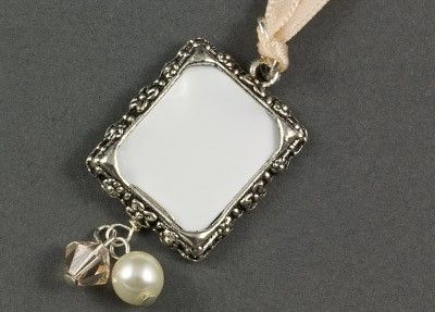 Bouquet Photo Frame Wedding Charm The Bouquet Photo Frame Wedding Charm is a pretty way to remember a loved one at your wedding by placing their photo into the frame and attaching it to your bouquet. The charm is embellished with a swarovski crystal bicone and pearl dangle. Each charm is presented in a pretty organza drawstring bag. Available in gold or silver and a fabulous range of bead and ribbon colours.