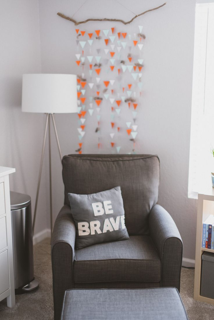 Be brave pillow, glider, modern tripod lamp, and DIY sewn paper triangle and feather garland wall hanging from our woodland adventure themed nursery in grey, white, orange, and mint.