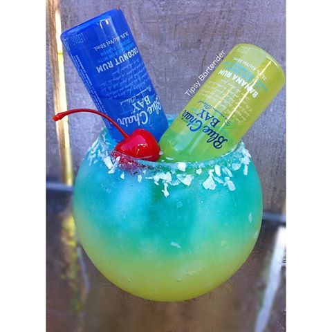 BAHAMA BLUES Yellow Layer 1 oz. (30ml) Pineapple Vodka  1 oz. (30ml) Pineapple Juice  1/4 oz. (7.5ml) Lime Juice   Blue Layer: 1/2 oz. (15ml) Coconut Vodka  1/2 oz. (15ml) Blue Curaçao  1/2 oz. (15ml) Blue Island Puckers  Top off with lemon lime soda  1 Mini Bottle of Banana Rum  1 Mini Bottke of Coconut Rum Rim with light agave Nectar & Coconut Garnish: Cherry