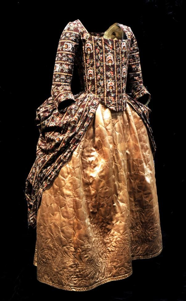 Side view, robe à l'anglaise, worn à la polonaise, England, 1770-1780. Hand block printed cotton, called 'dark ground chintz'; quilted gold silk satin petticoat.
