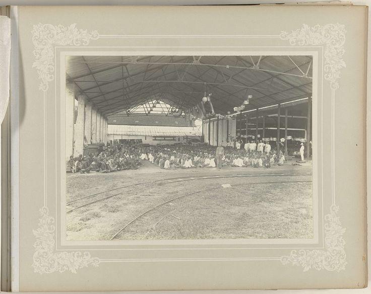 anoniem | Fabriekspersoneel, possibly O. Hisgen & Co., 1890 - 1910 | Groepsfoto van het personeel van de suikerfabriek Tjomal. De Indische werknemers zitten op de grond in een grote open hal. Op de voorgrond een smalspoor. Onderdeel van het fotoalbum over de suikerfabriek Tjomal (Comal) op Java in de periode 1890-1910.