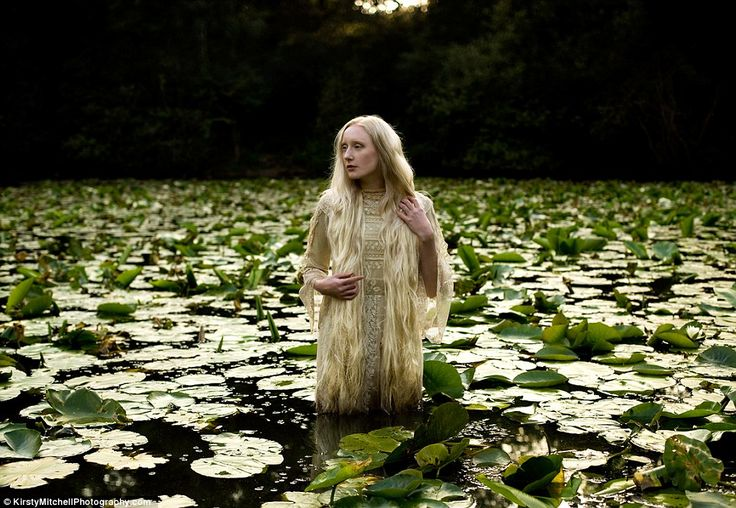 Lady of The Lake: a model emerges from a pool of lilies amidst the forest (Wonderland Series by Kirsty Mitchell)