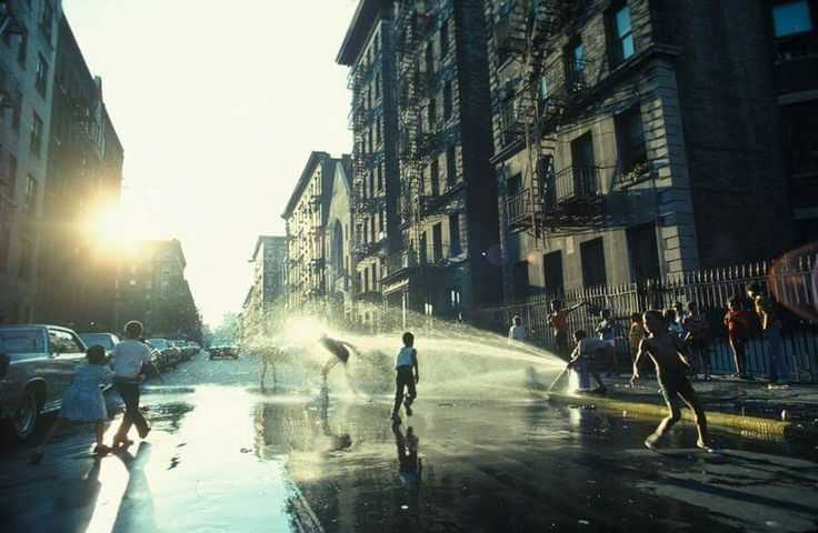 A fire hydrant refreshes youngsters on a hot day in Harlem, New York, 1977  Photo by Leroy H. Woodson