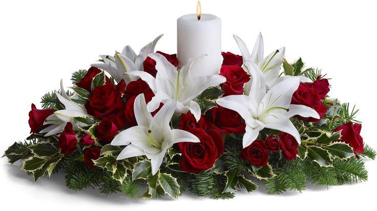 Cores clássicas do Natal neste belo arranjo  central de rosas vermelhas, lírios asiáticos brancos, ramos de abeto e azevinho. Uma única vela branca adiciona brilho sutil.   Fotografia: Teleflora.com.