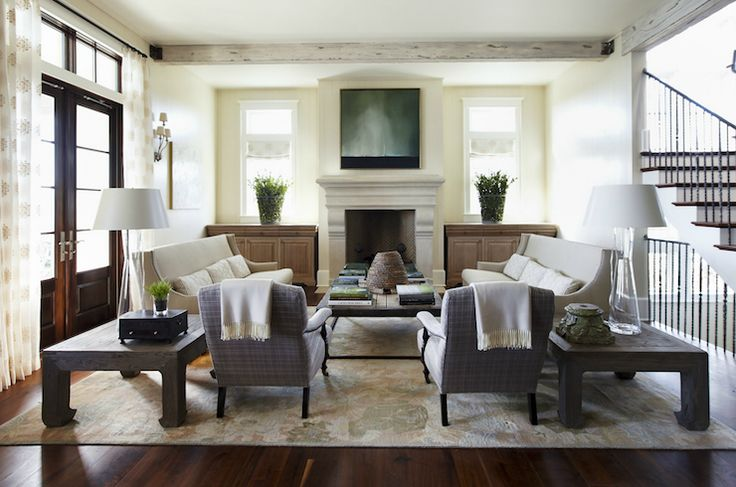 Beautiful living room with rustic box beams, limestone fireplace flanked by wood built-ins, pale yellow walls paint color, French doors & transom windows, gray curvy sofas, industrial cocktail table and glass hourglass lamps.