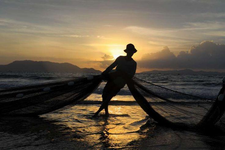 Dieser indonesische Fischer hat nachts gefischt. Im Licht der aufgehenden Sonnee holt er nun in Banda Aceh seine Netze ein.