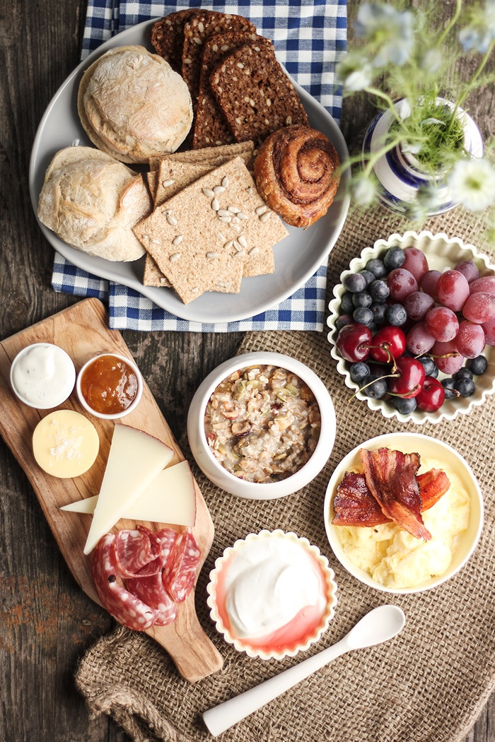 Brunch spread: fruits, cheeses, breads, oatmeal, bacon, scrambled eggs...