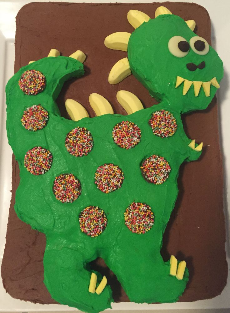 Homemade Dinosaur Cake for my son's 1st birthday - base: buttercake with chocolate buttercream. baked in a large slice tin. - dinosaur: buttercake with buttercream icing (green food colouring). baked in a wiltshire dinosaur mould - decorations: ALLEN'S Banana lollies, Freckles, chocolate melts.