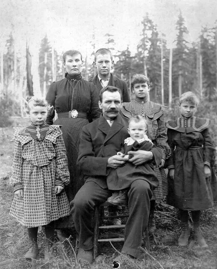 Washington State Pioneer Family - Circa 1900. When they gathered to record their claim to this land, every female member of the family wore jewelry. The mother wears an Arts & Crafts bar pin at her throat, a long watch chain with concealed watch, and a magnificent Victorian belt buckle. Each of the girls has an identical flower brooch at the center of their collar. In honor of the occasion the father and son put suit jackets over their work shirts.