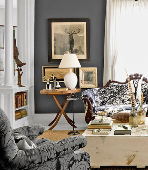 """The home's aesthetic took shape based on whatever Miller discovered at antiques shops or her rural auction house: birdcages, floral frogs, Victorian sofas, cryptic portraits. """"I buy cheap stuff,"""" Miller says. """"I just buy a lot of it."""" A palette of grays and browns creates a neutral, yet still dramatic, backdrop for the cabinet-of-curiosities vibe. Why it works: Get creative with seating. The rococo-revival sofa (right) wears Marimekko's Tuuli print, which turned the circa-1860s piece funky…"""