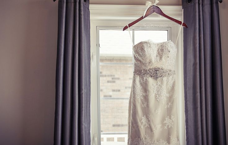 Beaded and laced wedding dress hanging in window | Vintage Wedding Photography | www.newvintagemedia.ca