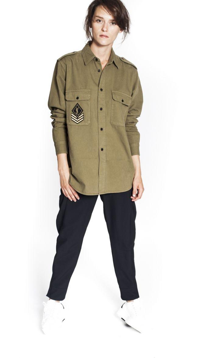 Military Khaki Shirt from Saint Laurent Cette chemise militaire est signée Saint Laurent. Elle est réalisée en coton kaki avec un patch YSL. Col revers, longues manches, coupe droite, 2 poches devant et fermeture boutons classique noirs.  100% Coton