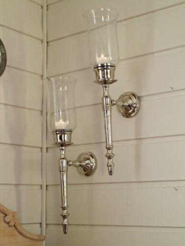 Lysestake til vegg m/glasskolbe H:50 cmMål: H:50 L:11 D:18 cm Farge: Sølv/klart glass Materiale: Aluminium/Glass