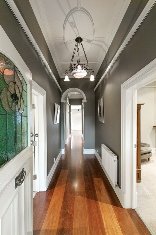 An inviting arched entrance hall featuring dark recycled Ironbark floors and ornate ceilings - captivating!