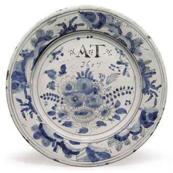 AN ENGLISH DELFT DATED CHINOISERIE PLATE 1697, PROBABLY BRISLINGTON Painted in shades of blue and outlined in black, the center with the initials ·A·T· above the date 1697 and a bouquet of fruit and flowers within concentric bands and a border of rockwork issuing foliage
