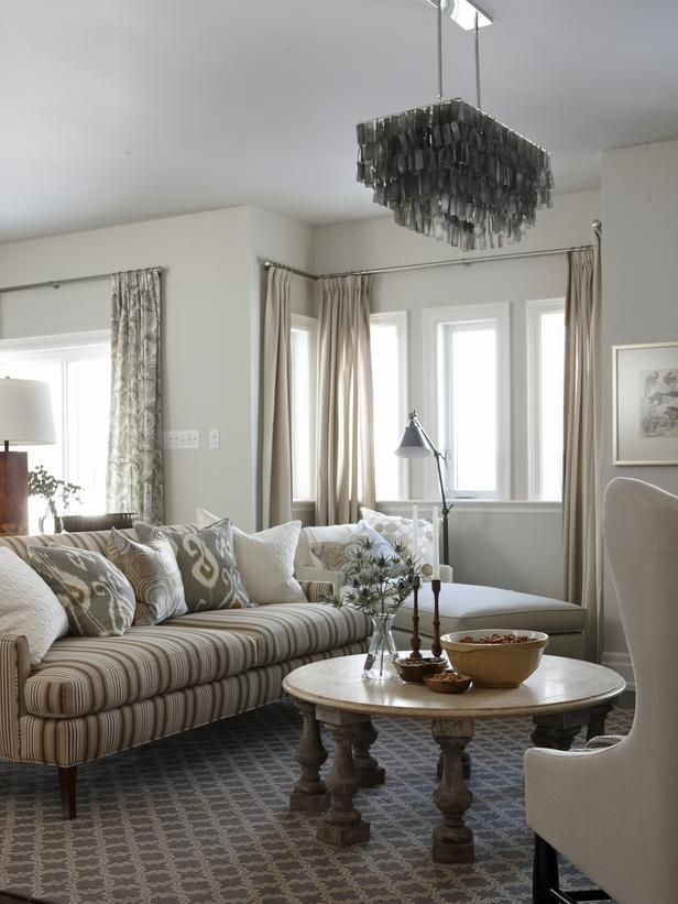 Sarah Richardson:  Just off the kitchen, Sarah created a cozy family room that's full of stylish-but-durable accents. A striped custom sofa anchors the space. To get the look of custom drapery for a fraction of the cost, Sarah added the striped sofa fabric to the edges of pre-made panels. Balusters from an architectural salvage shop form a base for an antique marble coffee table.