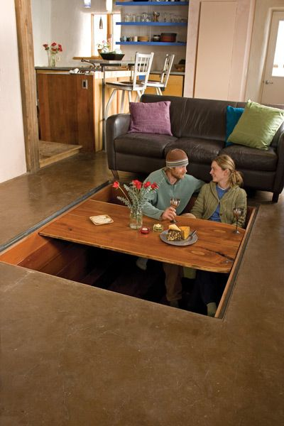 hidden dining room table- kinda crazy but cool. covered with wood planks and a coffee table when not in use