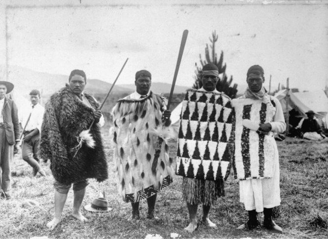 Ross, Malcolm, 1862-1930 Young men of Tuhoe wearing kakahu (cloaks) and kahu huruhuru (feather cloaks), and carrying taiaha, in Ruatoki during the visit of Lord Ranfurly and party