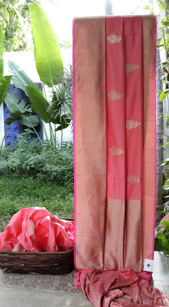 This punch pink Benares silk has gold bhuttas all over the sari. The border and pallu have intricately woven gold zari giving it just the perfect finish for celebrations and ceremonies